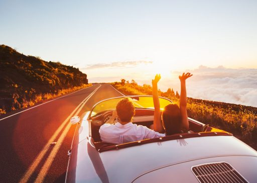 44182159 - happy couple driving on country road into the sunset in classic vintage sports car