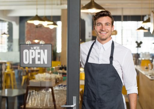 59968227 - portrait of smiling owner standing at his restaurant gate with open signboard. young entrepreneur leaning at the cafeteria door and looking at camera. chef or waiter standing in front of coffee shop.