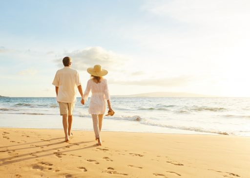 49643694 - happy romantic middle aged couple enjoying beautiful sunset walk on the beach. travel vacation retirement lifestyle concept